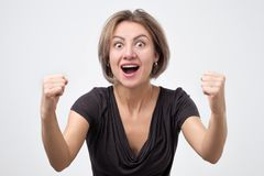 Young woman with raised hands shouting and celebrating success stock photography