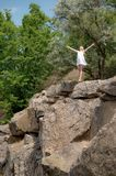 Young woman with raised hands sky on the edge of the cliff in su. Mmer day. Girl wearing short white dress Royalty Free Stock Images