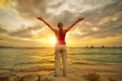 Young woman with raised hands standing on shore and looking to a Royalty Free Stock Photography