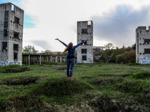 A young woman raised her hands to heaven In front of three collapsed buildings - View from the back. A gloomy landscape, a dark sky and a strong wind blows her Stock Photo