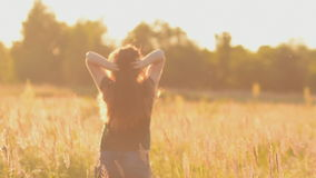 A young woman raises his arms for joy. In warm tones. stock footage