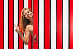 Young woman raising hand, showing v-sign fingers gesture. Happy smiling young blond woman against red striped wall of beach changing cabin has fun, raising hand Stock Photo