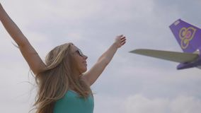 Plane flying above the woman. Young woman raising hands up watching at sky with plane,airplane passing overhead, young happy girl watching waving and jumping stock video footage
