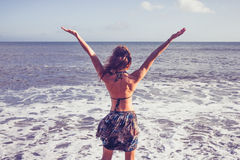 Young woman raising her arms at the beach Royalty Free Stock Photo