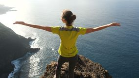 Young woman raising her arms on beautiful steep cliff over the ocean. Lady on the summit in beautiful scenery. stock video footage