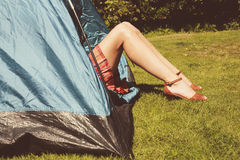 Young woman raising her legs from inside a tent Stock Images