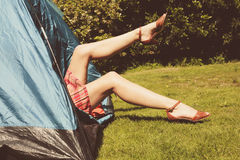 Young woman raising her legs from inside a tent Royalty Free Stock Images