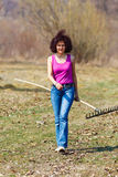 Young woman with a rake in an orchard Royalty Free Stock Image