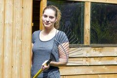 Young woman raking grass in garden Stock Photo