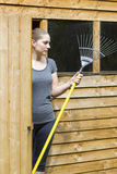 Young woman raking grass in garden Royalty Free Stock Images