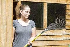 Young woman raking grass in garden Stock Images