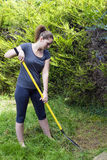 Young woman raking grass in garden Royalty Free Stock Photography