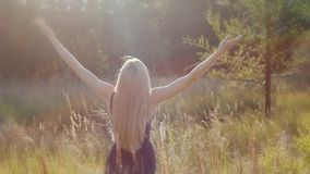 Young woman rase her hand to the sun. Freedom concept. Woman look at the sun and up her hands stock video footage