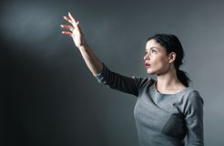 Young woman reach her hand at something. Young woman reach her hand on a solid background stock photography