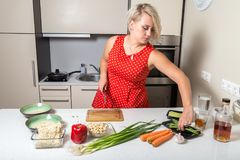 Young woman reaching for asparagus and holding knife in other ha. Girl reaching for asparagus and holding knife in other hand Stock Photography