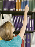 Young Woman Reaching For Book From Library Shelf Stock Photography