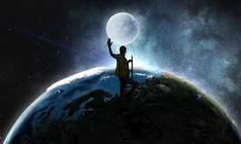 Young woman reaching moon royalty free stock photography
