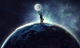 Young woman reaching moon stock photo