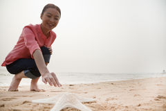 Young Woman Reaching Out for Starfish Stock Photo