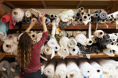 Young woman reaching to select fabric from storage shelves Royalty Free Stock Photo