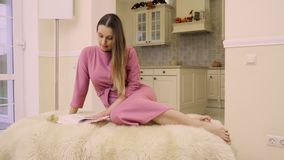 Young woman read book at home. Beautiful woman sits on the armchair and read the book. Pretty woman spend her leisure time alone at home with interesting stock footage