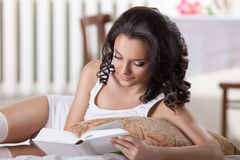 Young woman read book in morning interior Stock Photos