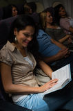 Young woman read book plane night flight Royalty Free Stock Image