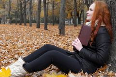 Young woman read book, sit on yellow leaves in autumn park near tree royalty free stock photos