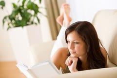 Young woman read book on sofa Stock Photos