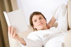 Young woman read book on sofa wearing bathrobe Royalty Free Stock Photos