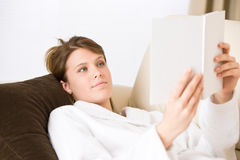 Young woman read book on sofa wearing bathrobe Stock Images