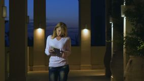 Young woman read the journal in huge hall with muffled light. Young woman stands in luxury villa in huge hall with columns and muffled light. Female read and stock video