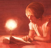 Young woman reading. By candlelight Royalty Free Stock Photo
