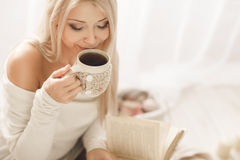 Young Woman Reading A Book And Drinking Coffee. Stock Images