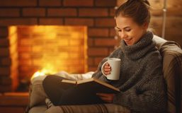 Free Young Woman Reading A Book By The Fireplace On A Winter Evenin Royalty Free Stock Photo - 108120285