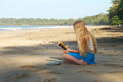 Young woman reading on beach Stock Photography