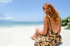 Young woman reading at the beach Stock Photography