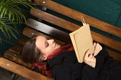 Young Woman Reading on Bench Royalty Free Stock Photography