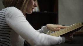 Young woman reading a big book in library. bookshelves with books stock footage