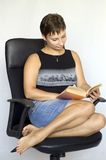 Young woman reading a book. While sitting in a chair Royalty Free Stock Photos