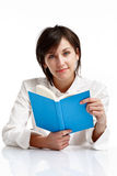 Young woman reading a book. Young woman with blue eyes reading a book, looking and smiling, on white background Stock Images