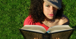 Young woman reading a book. Young attractive woman reading a book as the sun sets.  Banner is usable as copy space or can be cropped down for a tighter shot Stock Photo