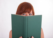 A young woman is reading a book Stock Image
