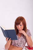 A young woman is reading a book Royalty Free Stock Image