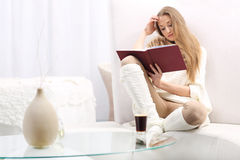Young woman reading a book. Long-haired young blonde women reading a red book sitting on the sofa. On the table, a cup of coffee Royalty Free Stock Images