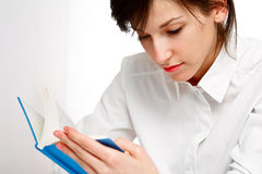 Young woman reading a book with attention. Young woman reading with attention, on white background royalty free stock photography