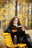 Young woman reading book in autumn park Royalty Free Stock Image