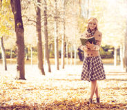 Young woman reading a book in an autumn park Royalty Free Stock Photo