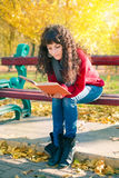 Young woman reading a book in autumn park. Young beautiful woman reading a book in autumn park Royalty Free Stock Photo