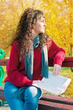 Young woman reading a book in autumn park. Young beautiful woman reading a book in autumn park Stock Photography